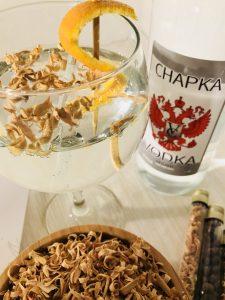 afbeelding van een glas wodka met botanicals en een fles wodka