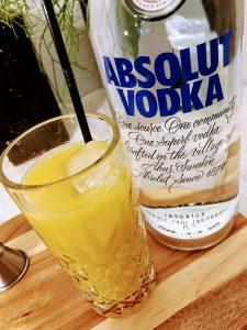Afbeelding van een glas screwdriver cocktail en een fles wodka