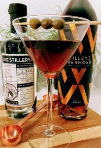 afbeelding van een glas wodka martini met olijven, een fles vermouth en een fles wodka